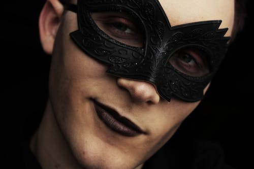 Handsome young male with makeup and black Colombina mask on face looking away on black background