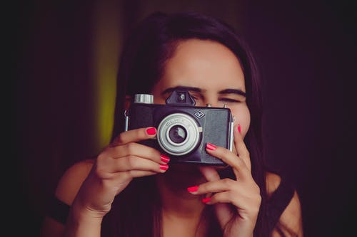 Young woman taking photo on old photo camera
