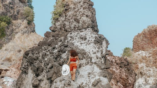 Woman in White Hat Sitting on Rock