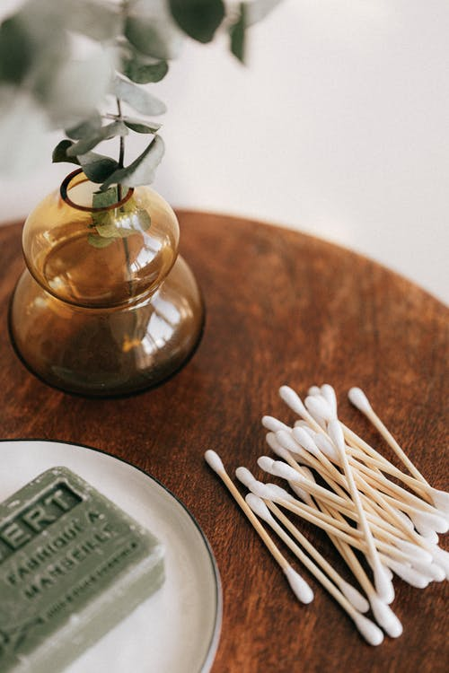 Set of ear sticks placed on wooden table with soap and decorative vase