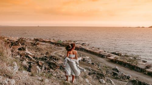 Woman in White Dress Sitting on Rock Formation Near Sea
