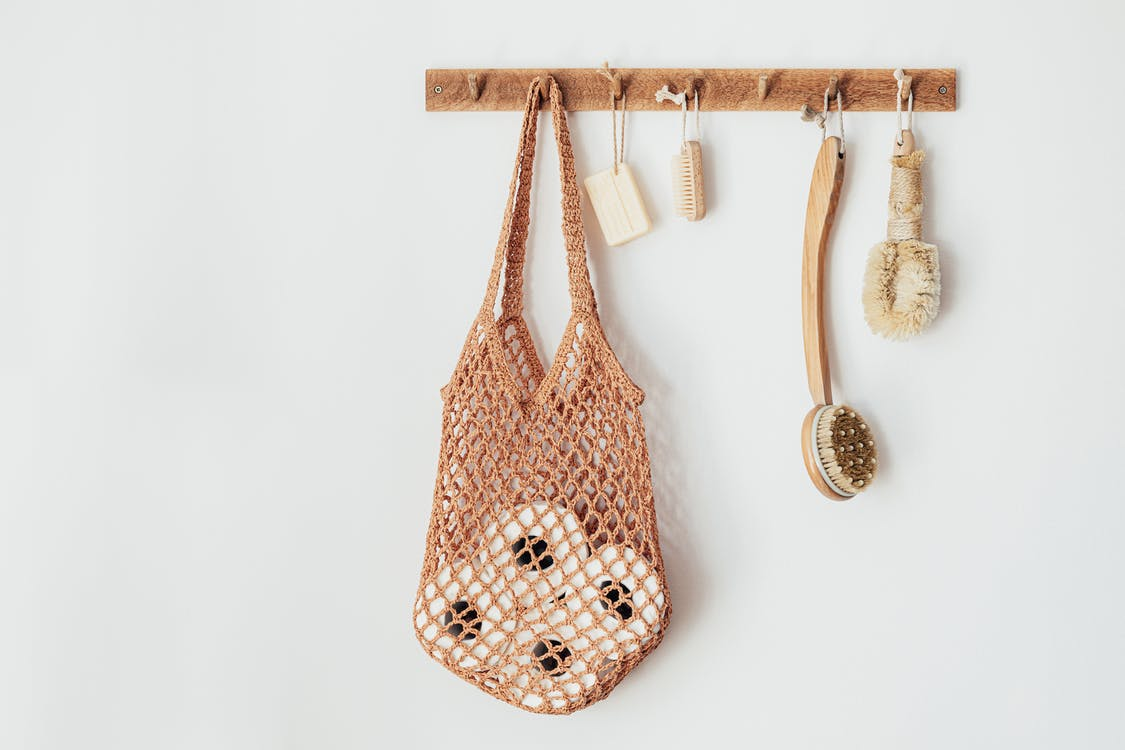 Composition with assorted wooden body brushes of different sizes with organic soap and string bag filled with toilet paper rolls hanging on wooden hanger on white wall in bathroom