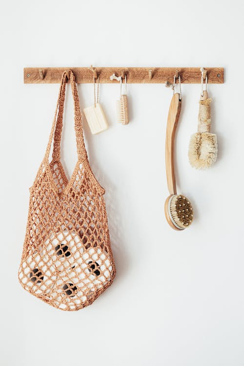 Body brushes and toiletries on wooden hanger