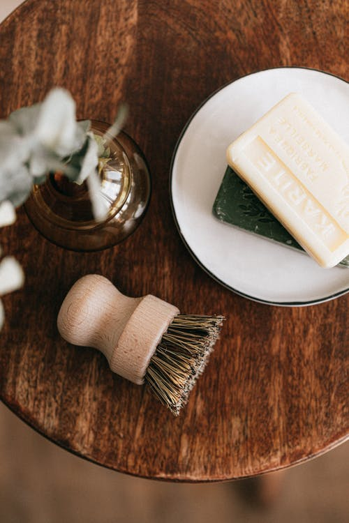 Natural soaps and shaving brush with vase on table