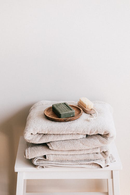 Natural toiletries and towels on stool