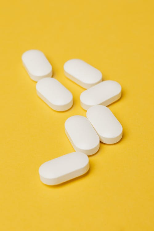 Heap of white pills on yellow surface