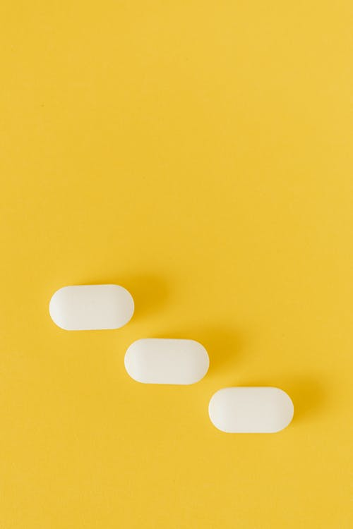 Top view composition with white ellipse shaped pills lying diagonally on lower part of yellow background