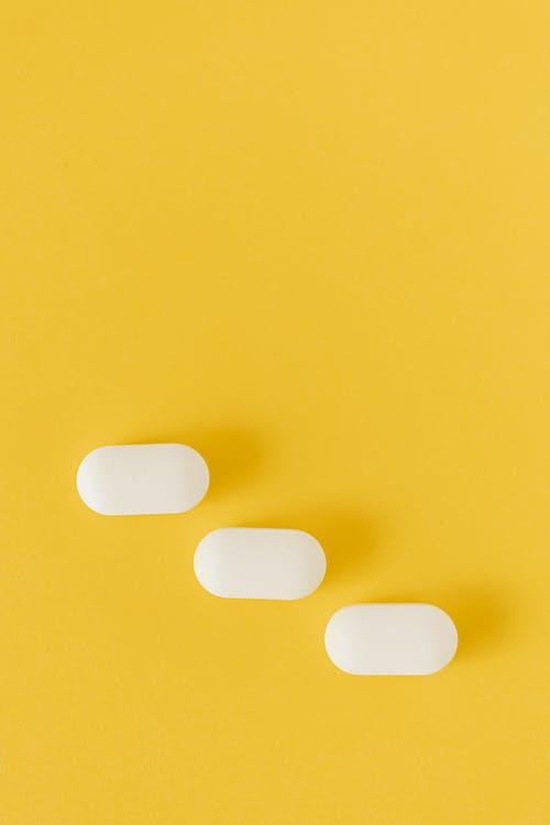 White pills on vivid yellow background