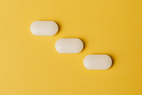 Set of pills on yellow surface