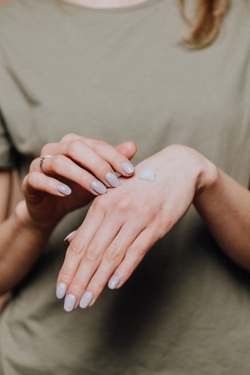 Crop anonymous female in casual outfit with stylish manicure and ring demonstrating small hand cream drop on back of hand