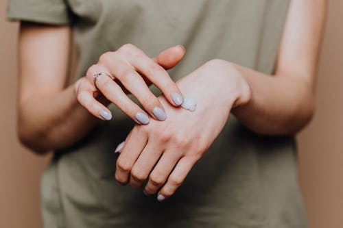 Crop anonymous female in casual shirt with manicured hands and ring softly rubbing hand moisturizer in back of hand skin