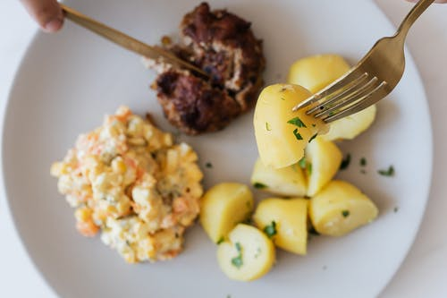 Plate with boiled potatoes Russian salad and meat cutlet