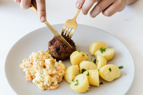 From above of crop anonymous person cutting with cutleries fried juicy meat cutlet served on white plate with tasty boiled potatoes and Russian salad