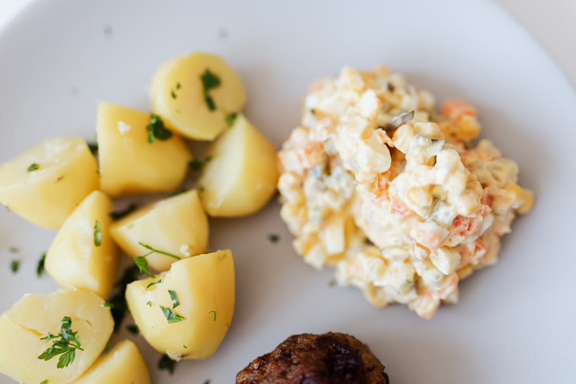 Boiled potatoes near traditional Russian salad