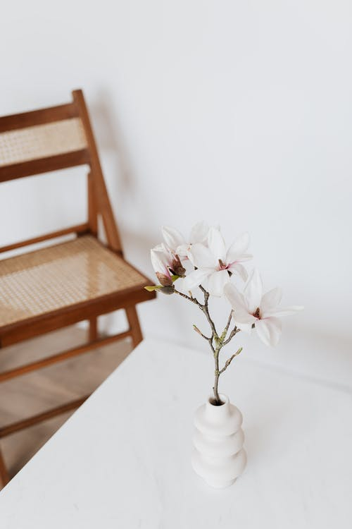 Chair near table with vase and flower
