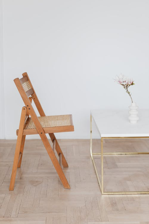 Comfortable wooden net chair located near white top table with vase and pink flower placed on light beige parquet against plain white wall