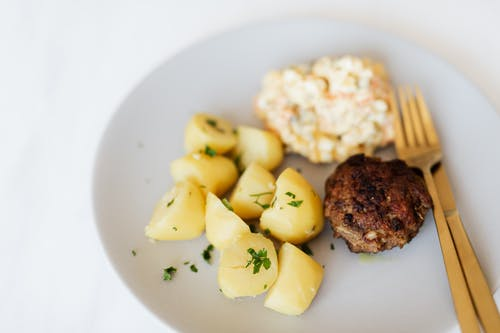 Fried meat cutlet served with boiled potatoes and salad