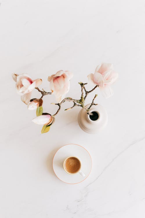 Vase with flowers and cup of espresso