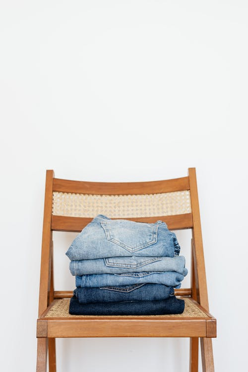 Stack of blue jeans of different shades on modern wooden chair against white wall