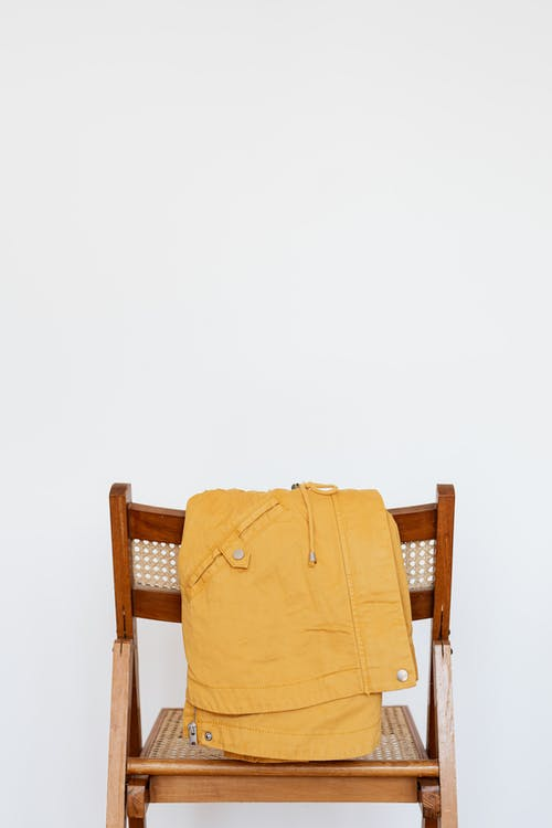 Yellow parka on wooden chair