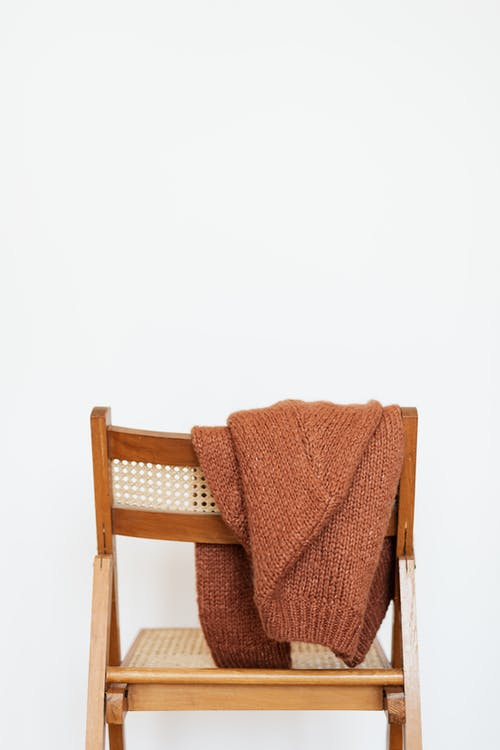 Brown coarse wool sweater hung on back of woooden chair against white wall