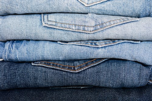 Closeup of stack of blue denim pants neatly arranged according to color from lightest to darkest