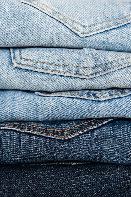 Stack of blue jeans arranged by color