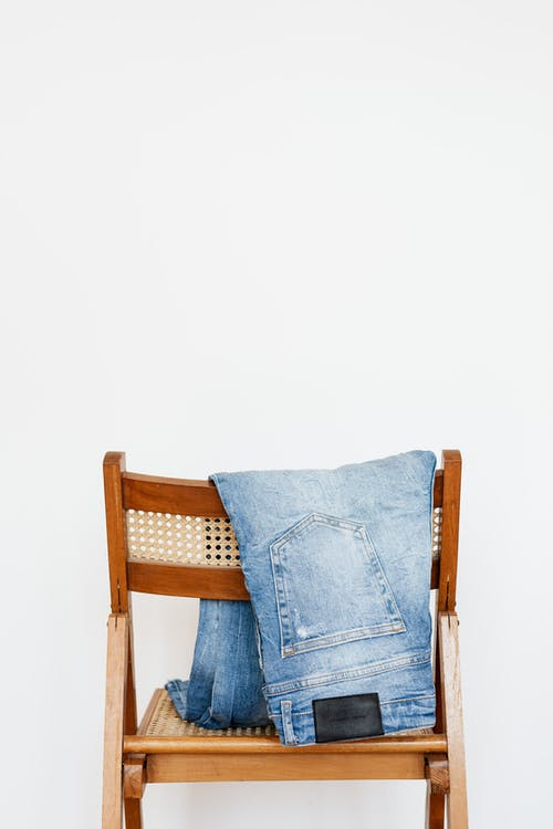 Trendy blue jeans put on back of wooden chair near empty white wall