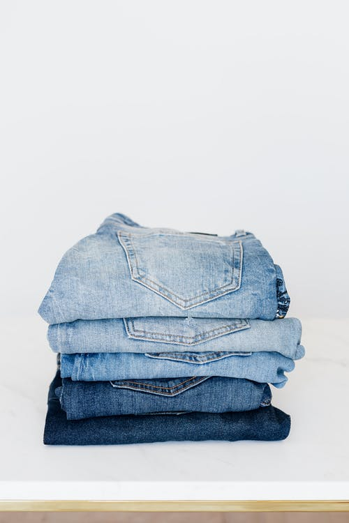 Pile of denim pants of different shades of blue placed on white shelf