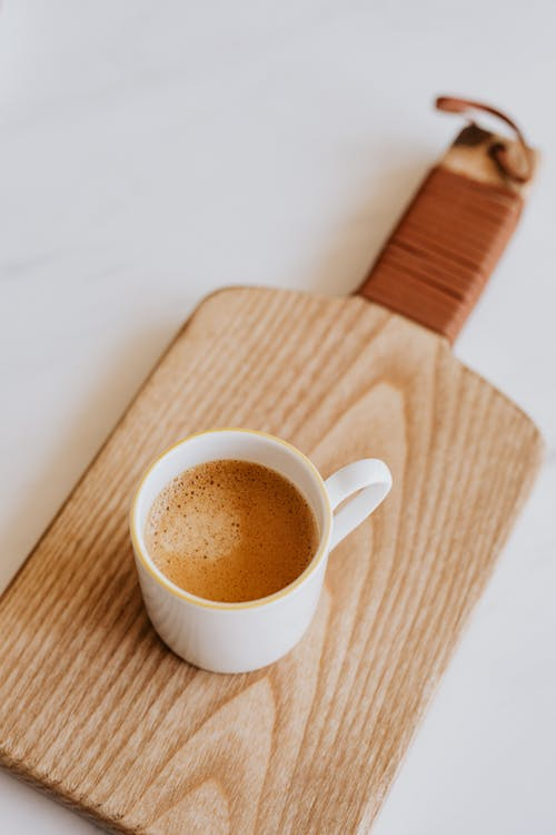 Coffee in white cup placed on cutting board