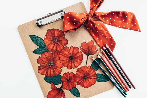 Overhead view of long multi colored pencils and red polka dot bow with ribbon on carton clipboard decorated with picture of red flowers with green leaves on white background