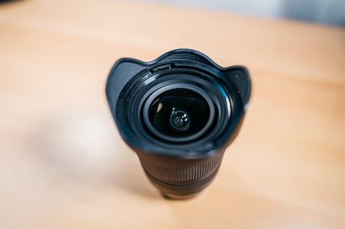 From above closeup of professional lens of modern photo camera placed on wooden table