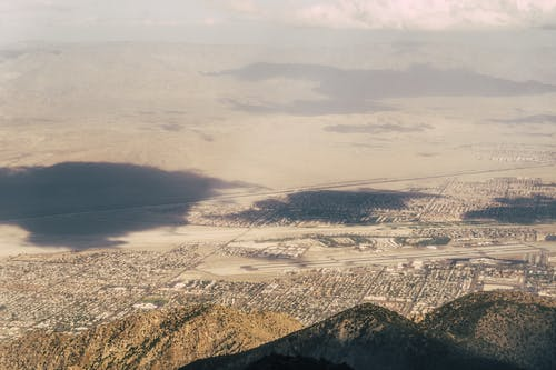 Aerial view of peaceful town located on desert terrain surrounded by hills and mountains on sunny day