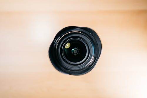 Lens of black photo camera placed on table