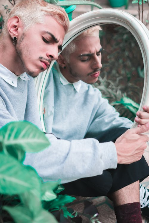 Crop stylish mindful man reflecting in mirror in garden