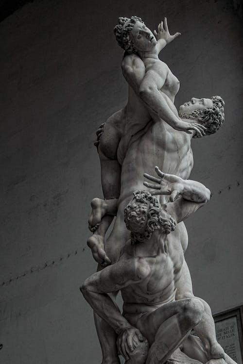 Old stone sculpture representing men raping woman