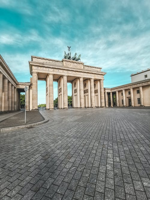 From below of aged masonry gate with quadriga statue on top under blue cloudy sky in Berlin