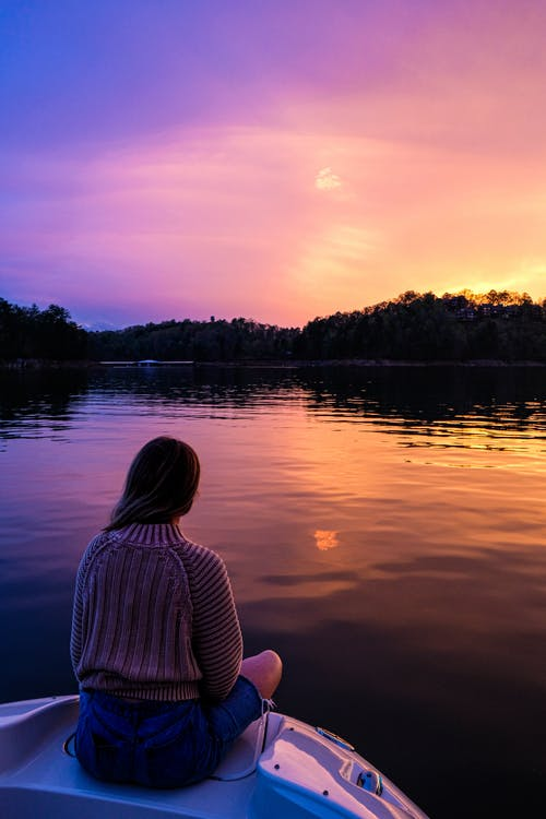 Photo of Woman Sitting on Boat While Looking at Sunset