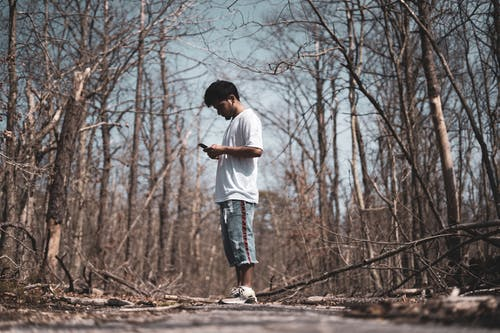 Photo of Man Standing While Using Smartphone