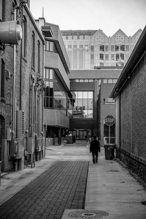 Grayscale Photo of Person Walking on Alley