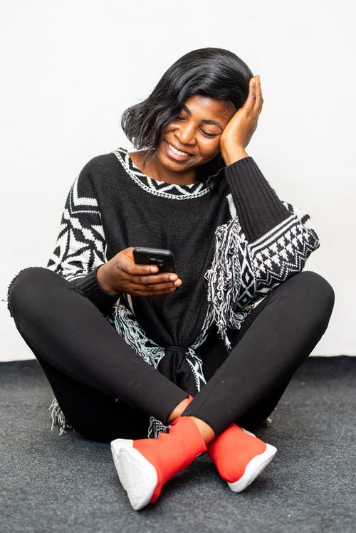 Photo of Woman Smiling While Using Black Smartphone