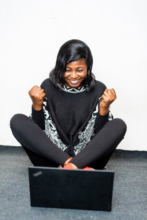 Excited black woman showing yes gesture near laptop