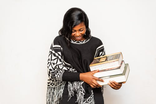 Happy black student with pile of books