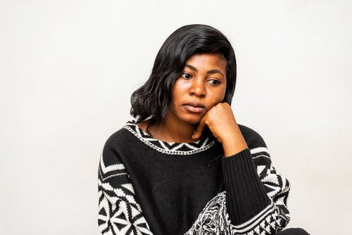 Young upset black female in stylish knitted sweater sitting leaned on hand near wall while looking away