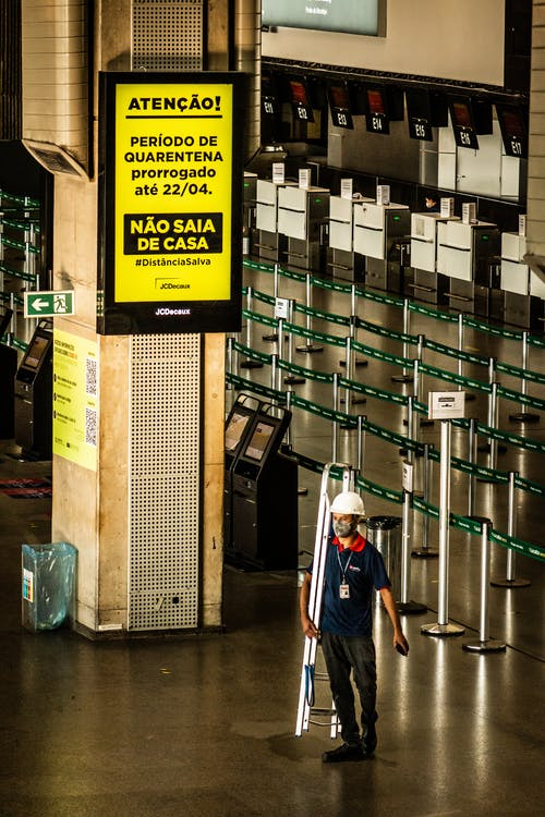 Unrecognizable workman with ladder in airport under bright signboard