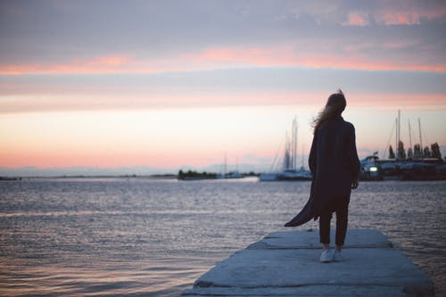Woman Standing on a Dock during Sunset