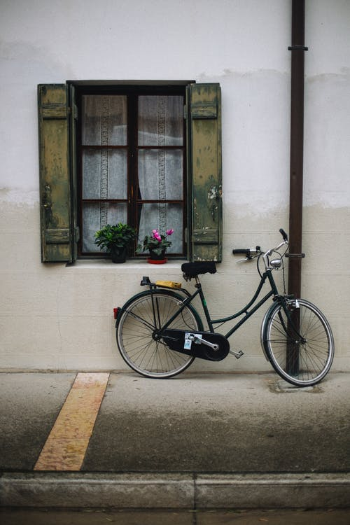 bicycle Parked Beside Green Wooden Window