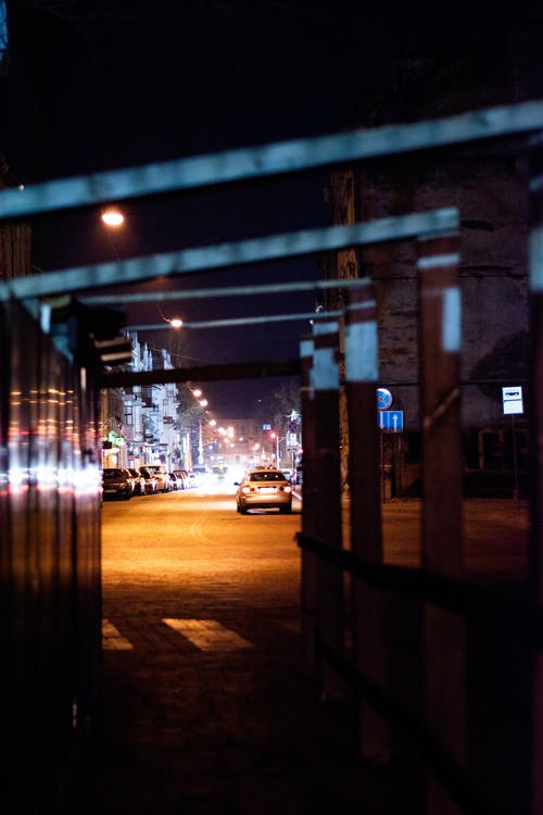 Night city road with cars near metal construction