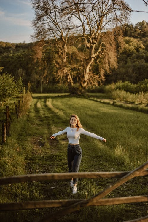 From above of young happy female with reached arms walking on green meadow behind mountain and looking at camera
