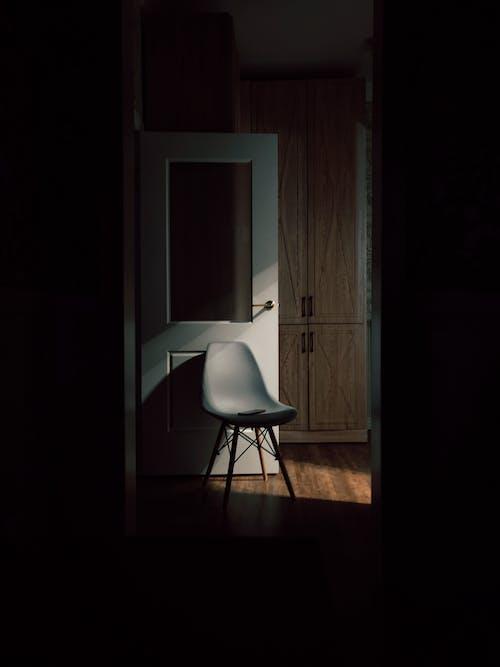 Chair near open door on wooden floor
